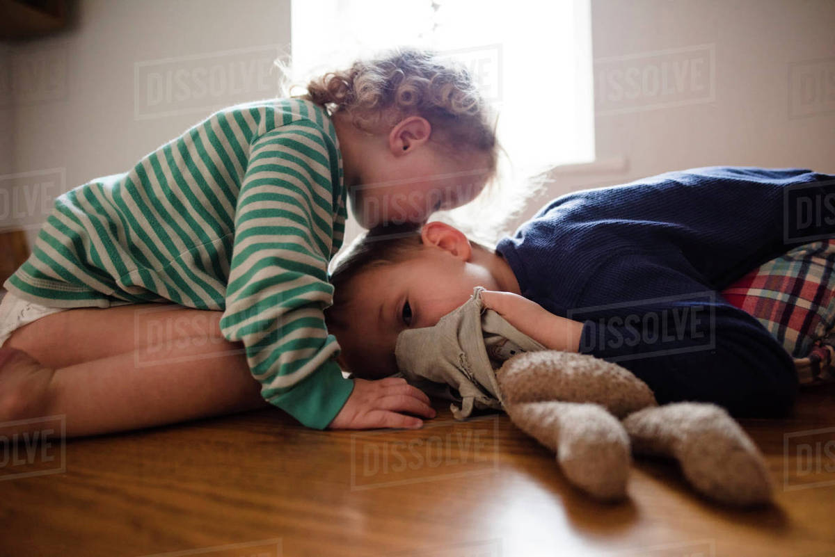 Side view of girl kissing brother on head at home stock photo