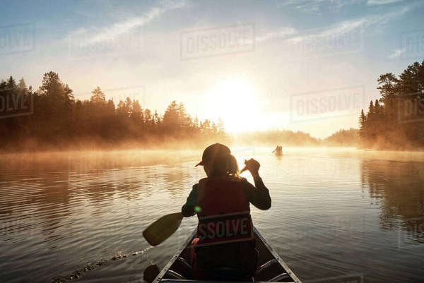 Rear view of woman traveling in boat on lake Royalty-free stock photo