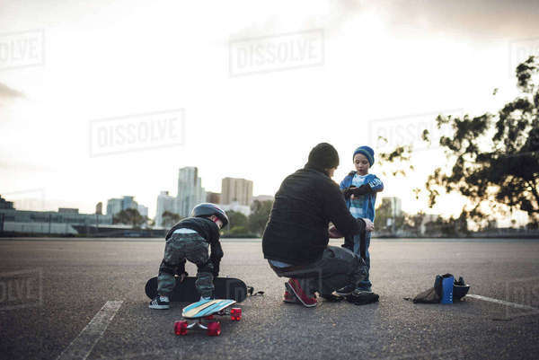 Father assisting sons in preparation for skateboarding at field Royalty-free stock photo