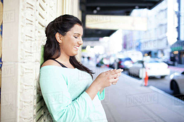 Smiling woman using smart phone while leaning on wall at footpath Royalty-free stock photo