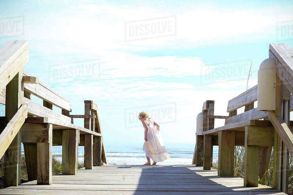 Rear view of girl standing on pier against sky Royalty-free stock photo