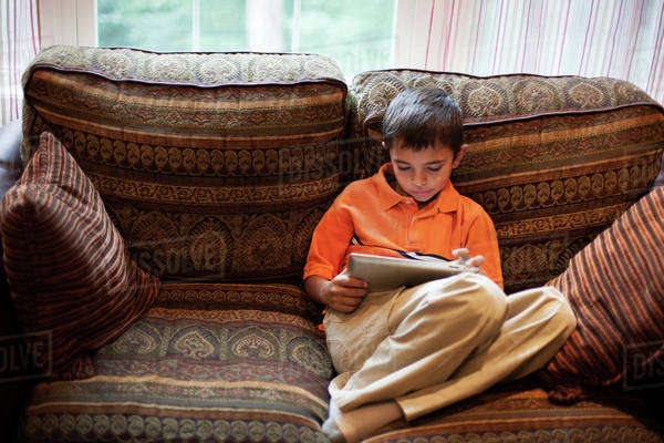 Young boy (8-9) using digital tablet on couch Royalty-free stock photo