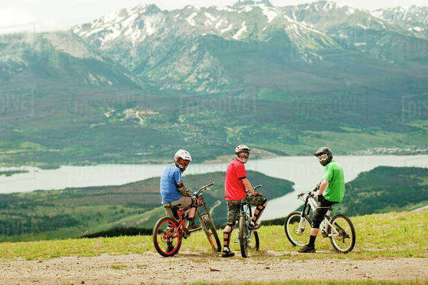 Three Mountain bikers and view of Valley Royalty-free stock photo