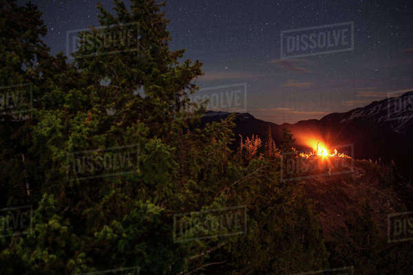 View of campfire glowing on field against star field at night Royalty-free stock photo