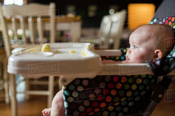 Baby girl looking away while sitting on high chair at home Royalty-free stock photo