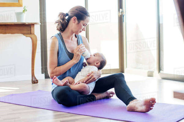 Mother feeding baby boy while sitting on exercise mat at home Royalty-free stock photo