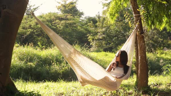 Lockdown shot of woman relaxing on hammock at forest during sunny day Royalty-free stock video