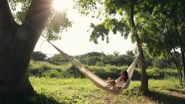 Lockdown shot of woman reading book while resting on hammock in forest during sunny day Royalty-free stock video