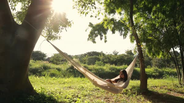 Lockdown shot of woman in sunglasses reading book while resting on hammock in forest Royalty-free stock video