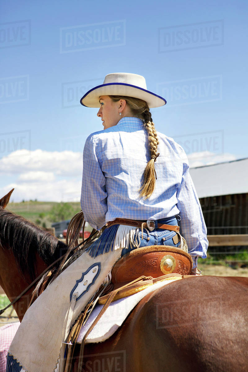 c041f3119 Cowgirl on her horse wearing chaps and cowboy hat stock photo