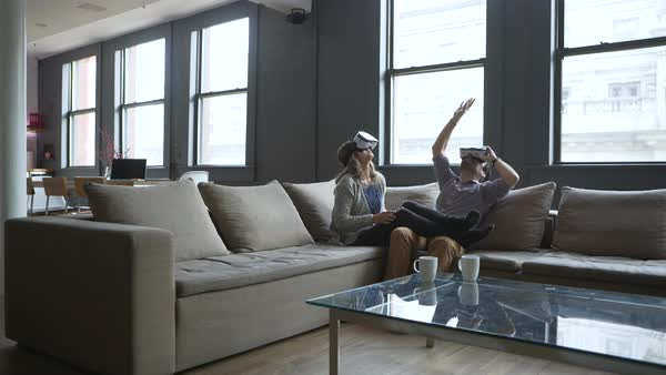 Dolly shot of business people wearing virtual reality simulator while sitting on sofa Royalty-free stock video