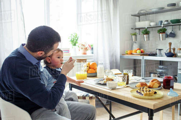 Father feeding breakfast to son at table in kitchen Royalty-free stock photo