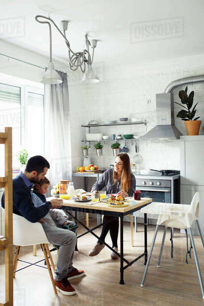Parents with son having breakfast at table in kitchen Royalty-free stock photo