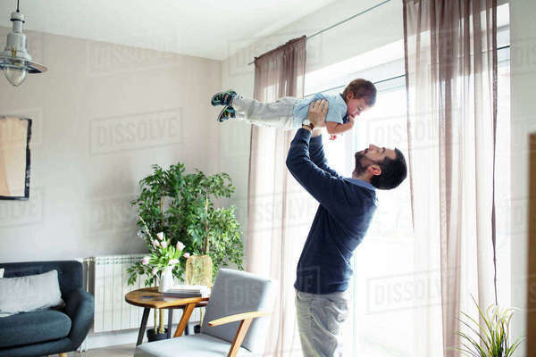 Playful man carrying son while standing by window at home Royalty-free stock photo