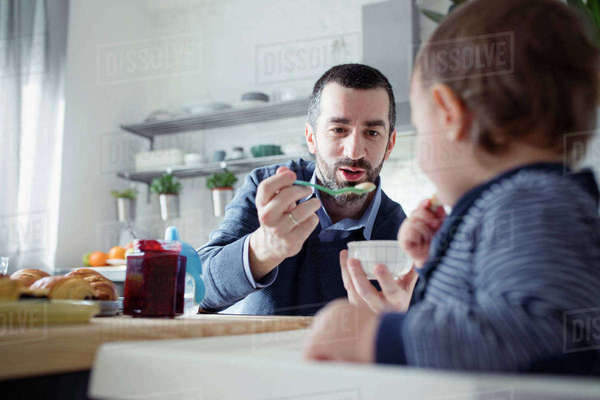 Father feeding breakfast to son sitting in high chair at home Royalty-free stock photo