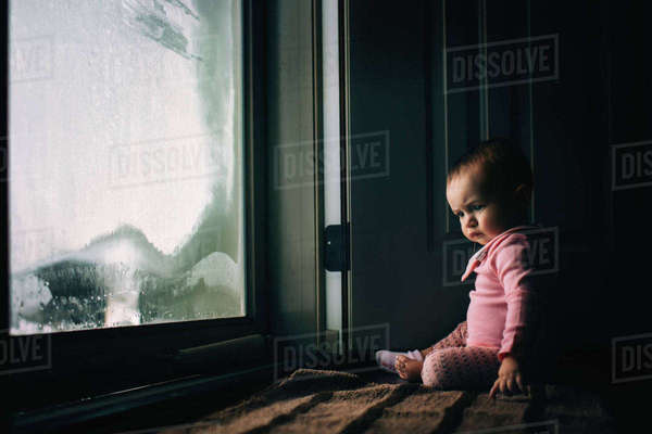 Baby girl sitting by condensed glass door at home Royalty-free stock photo