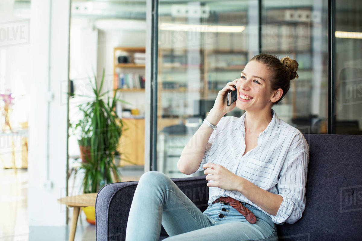 Happy Businesswoman Talking On Mobile Phone While Sitting At Office Stock Photo