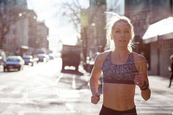 Confident female athlete running on city street during sunny day Royalty-free stock photo