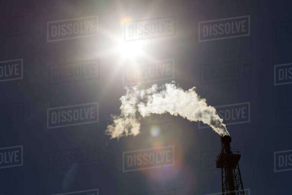 Low angle view of smoke emitting from chimney at oil refinery during sunny day Royalty-free stock photo