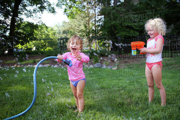 Happy sisters playing in backyard Royalty-free stock photo
