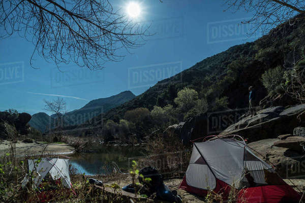 Side view of man standing on rock by lake at campsite Royalty-free stock photo