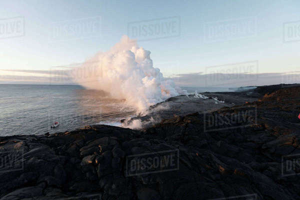 Smoke emitting from volcano at shore against sky Royalty-free stock photo