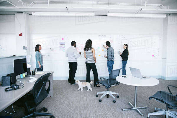 Business people writing notes on whiteboard white discussing in office Royalty-free stock photo