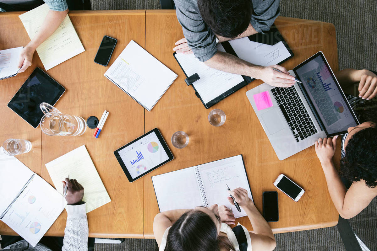 High angle view of business people analyzing data in meeting at board room - Stock Photo - Dissolve