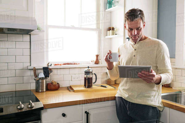 Man using tablet computer while leaning on kitchen counter at home Royalty-free stock photo