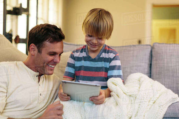 Father with son using tablet computer while sitting at home Royalty-free stock photo