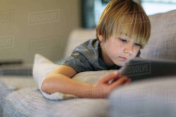 Close-up of boy using tablet computer while lying on sofa at home Royalty-free stock photo