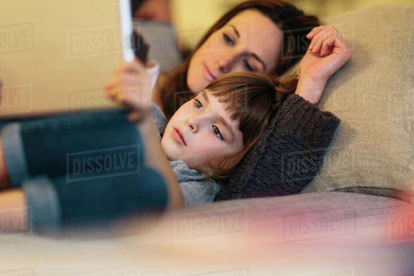 Mother and daughter using tablet computer while lying on sofa at home Royalty-free stock photo