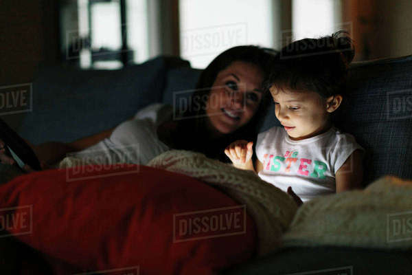 Woman looking at daughter using tablet computer at home Royalty-free stock photo