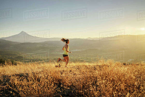 Full length of woman jogging on mountain against clear sky Royalty-free stock photo