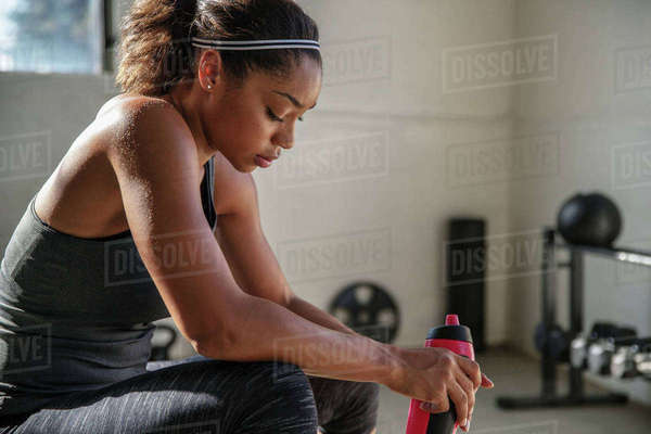 Side view of female athlete holding water bottle relaxing in gym Royalty-free stock photo