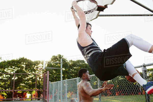 Friends playing basketball at court against clear sky Royalty-free stock photo