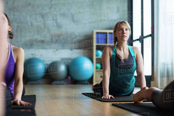 Women practicing upward facing dog position in gym Royalty-free stock photo