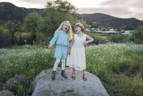 Playful sisters singing while standing on rock at park Royalty-free stock photo