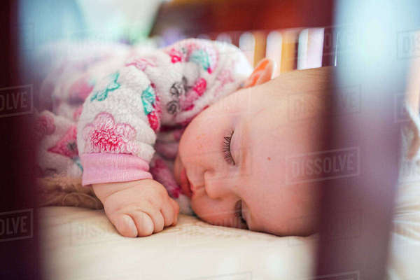 Close-up of cute baby girl sleeping in crib Royalty-free stock photo