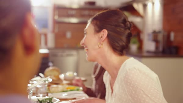 Handheld shot of happy friends talking while sitting at dining table Royalty-free stock video