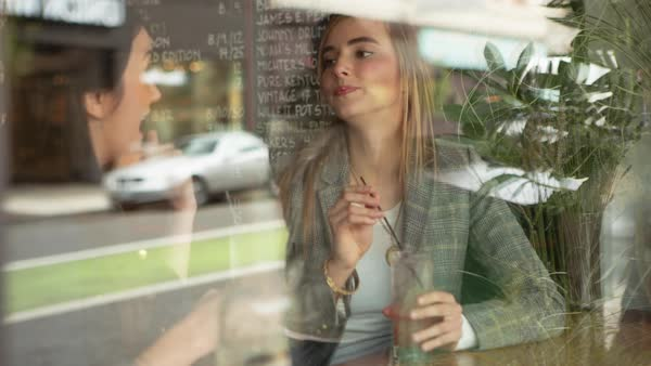 Handheld shot of friends talking while having drink in restaurant seen through window Royalty-free stock video