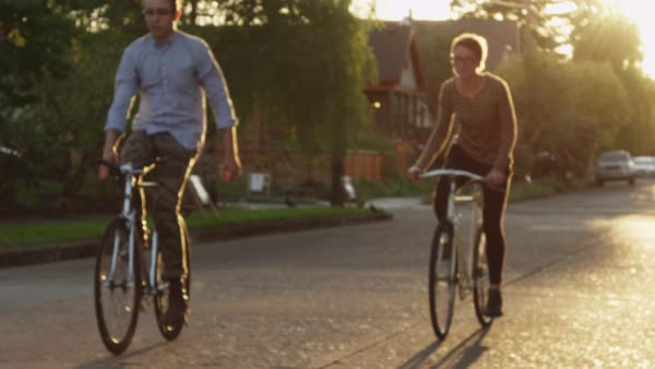 Slow motion of friends cycling on road during sunny day Royalty-free stock video