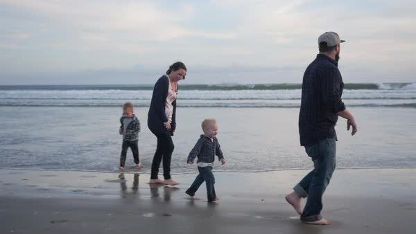 Handheld shot of boys with parents on shore at beach against sky Royalty-free stock video