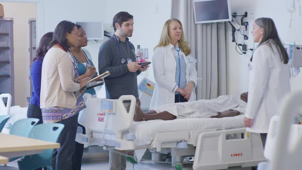 Handheld shot of female doctor training coworkers in hospital ward Royalty-free stock video