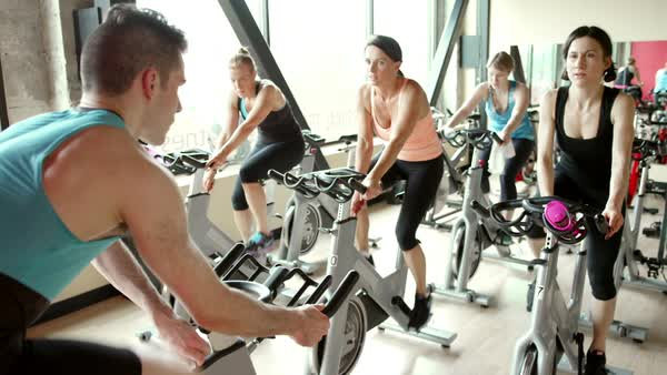 Handheld shot of male instructor guiding women while cycling on exercise bikes at gym Royalty-free stock video