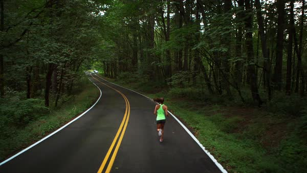 Handheld shot of female athlete jogging on road in forest Royalty-free stock video