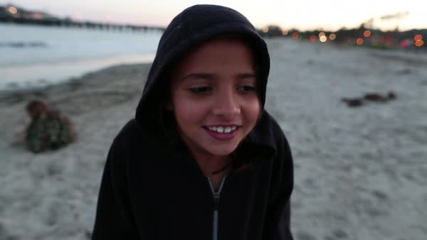 Handheld shot of girl shivering while standing at beach during sunset Royalty-free stock video