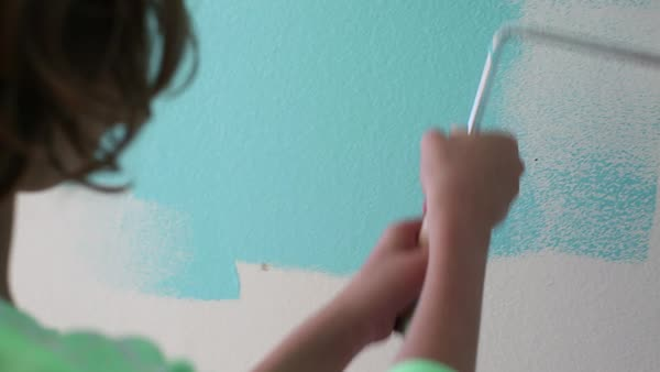 Handheld shot of girl using paint roller while painting on wall Royalty-free stock video