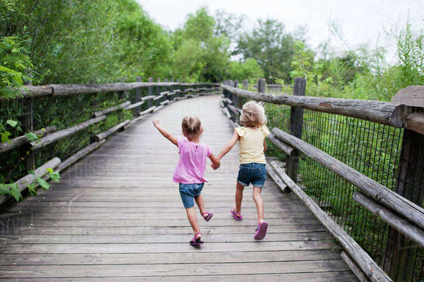 Rear view of sisters holding hands while running on footbridge amidst trees Royalty-free stock photo