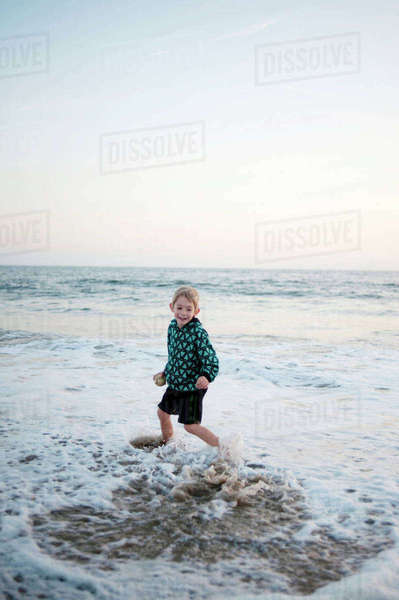 Smiling boy playing on shore at beach against sky Royalty-free stock photo